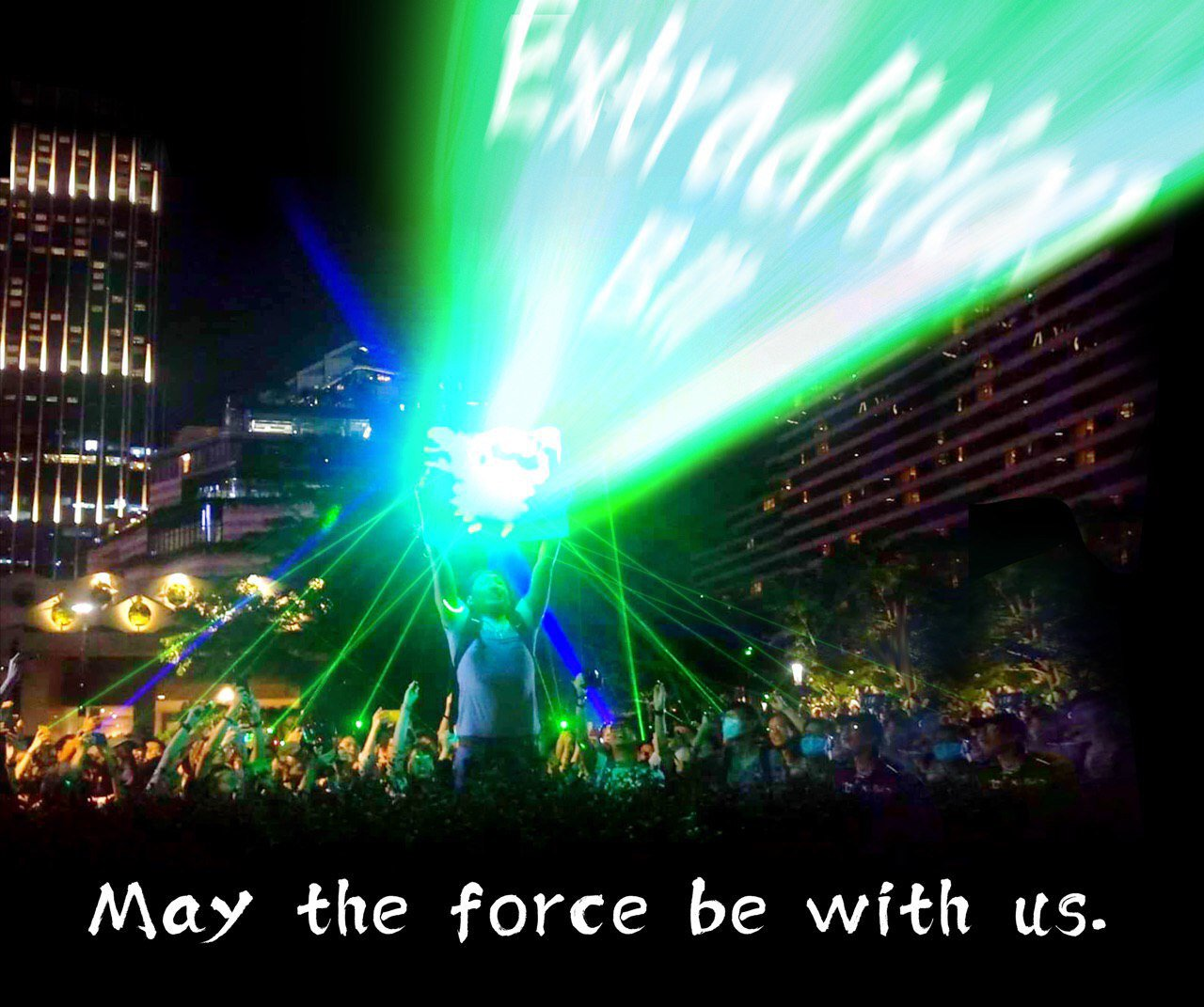 "Modified photograph of a protestor holding up a reflector, on which other people are aiming blue and green laser pointers. The beam from the reflector has been edited to read ""Extradition Bill"" in white. The image is captioned, ""May the force be with us."""