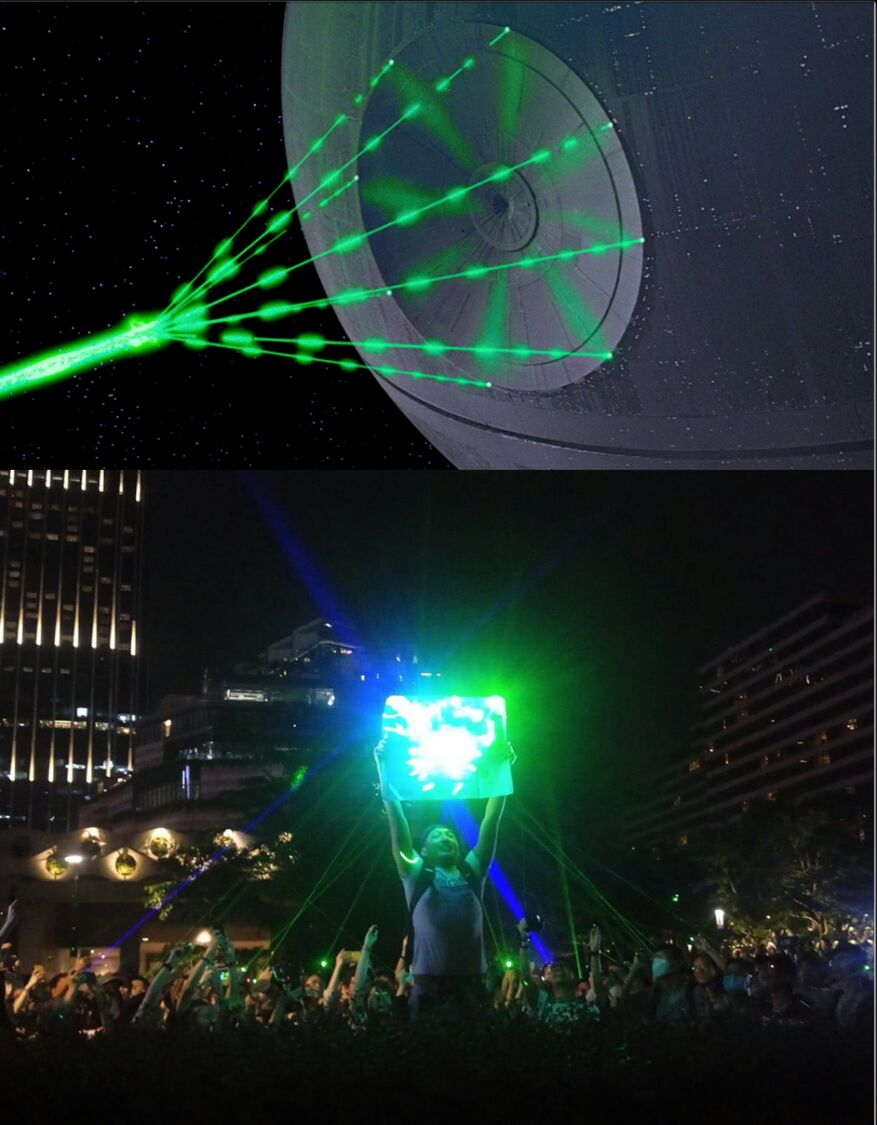 Two images. Top image is of the Death Star getting ready to fire a green beam of light. Bottom image is a photograph of a protestor holding up a reflector, into which the surrounding people are shining blue and green laser pointers, implying that the protestor in the bottom image is deflecting the shot from the Death Star.