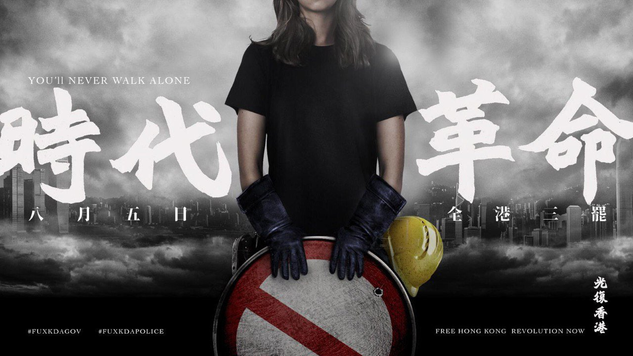 A modified photo of a young woman, her face out of shot, holding a makeshift shield made from a road sign. She is wearing a black short-sleeved tshirt and heavy-duty black gloves, with a yellow hard hat hanging from her hip. The background is a foggy black-and-white photo of the Hong Kong skyline. Text, in white, reads: You'll never walk alone (English), Revolution of Our Times (Chinese), Aug 5,  general strike across Hong Kong (Chinese). At the bottom are two hashtags, #FUXKDAGOV and #FUXKDAPOLICE, and the other half of the slogan: Free Hong Kong Revolution Now (English), Liberate Hong Kong (Chinese).
