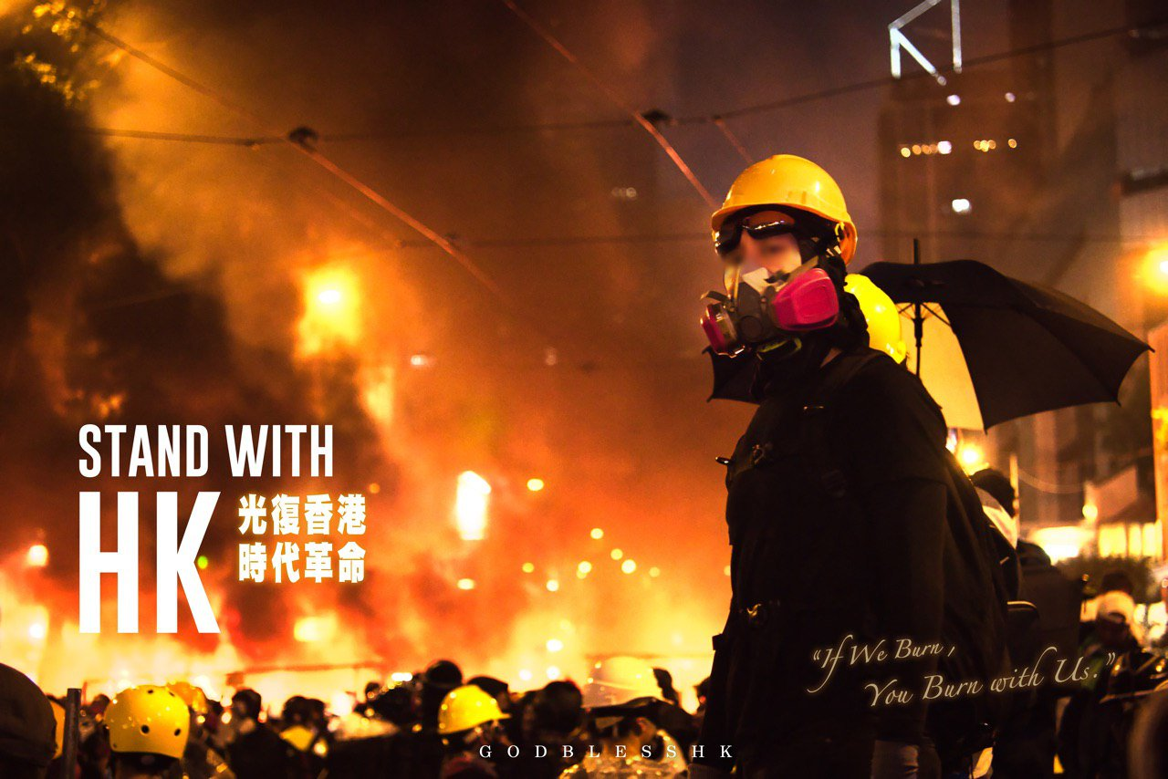 A photograph of a young frontliner in hard hat, goggles and respirator, standing against an out-of-focus backdrop of a street filled with protestors. It looks like the air is filled with gas and the glow suggests a fire in the back. Text on top, mainly English: Stand with HK. In Chinese: Liberate Hong Kong, Revolution of Our Times. English: If We Burn, You Burn With Us. God Bless HK.