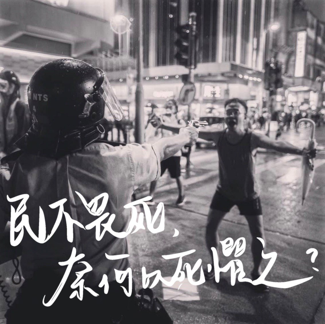 "A black and white photo of a man, arms outstretched, unarmed and dressed in a tank top, shorts and flip flops, standing in front of a riot police officer aiming a revolver in his direction. On top is a caption in Chinese: ""When the people do not fear death, what do they fear?"""