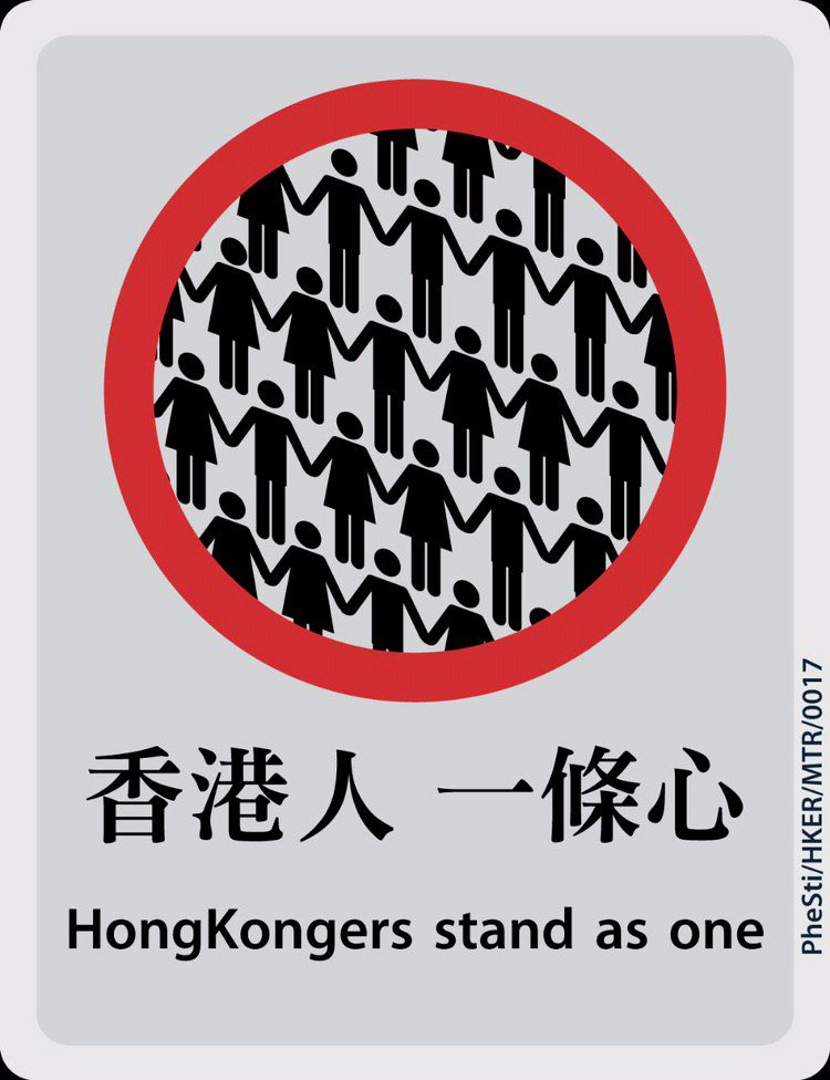 "An MTR style poster, featuring a simple heavily stylized illustration of a human chain inside a red circle. The caption, in Chinese and English, reads, ""HongKongers stand as one""."