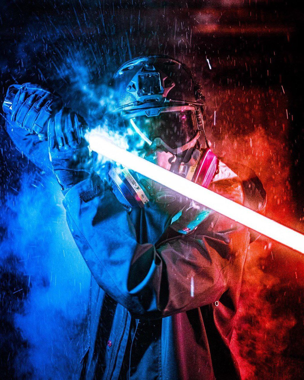 An edited photograph of a protestor in helmet, ballistic goggles and half-face respirator. They are wearing heavy-duty gloves and wielding a lightsaber. The protestor is standing in the rain against a smoky backdrop. The left side of the image is lit up in blue, while the right-hand side is in red.